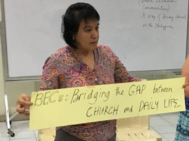 "Eine Frau aus den Philippinen hält ein Banner mit der Aufschrift ""Bridging the GAP between CHURCH and DAILY LIFE""."